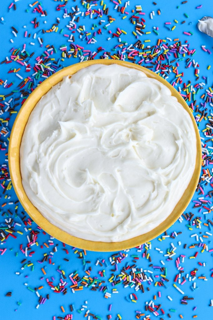 Top down view of a bowl full of cream cheese frosting surrounded by sprinkles on a blue background.