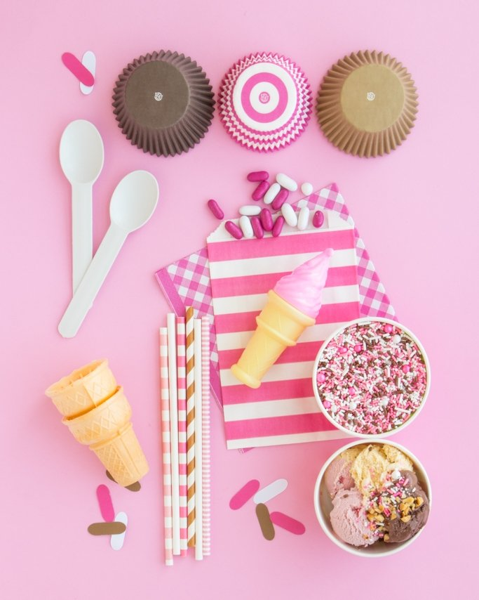 Neapolitan ice cream party supplies on pink background