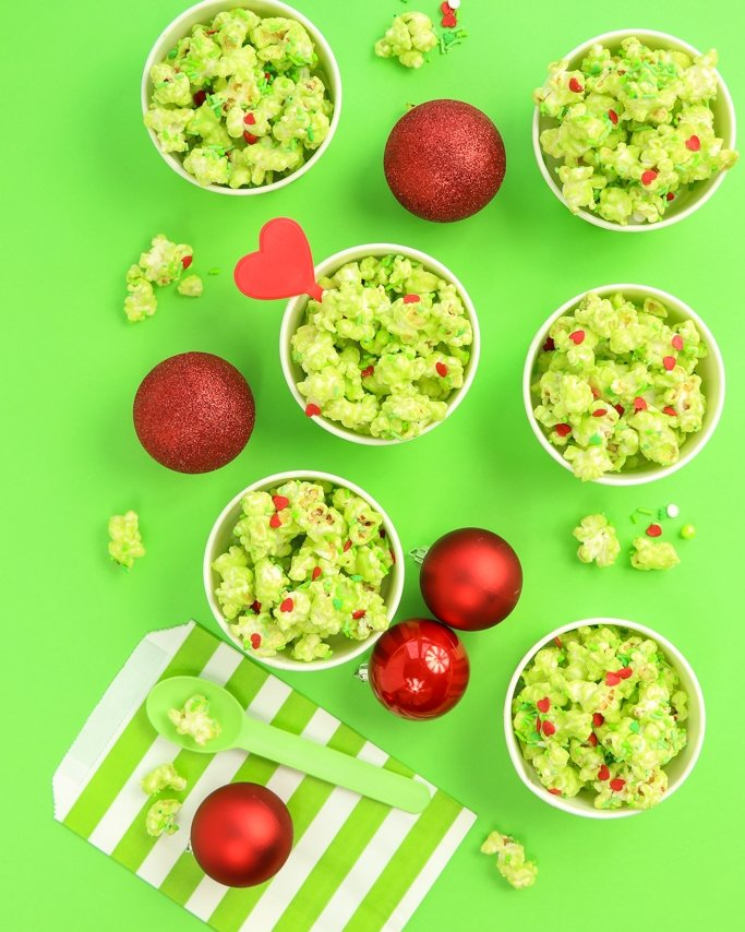 Grinch Popcorn in green striped treats cups on lime green background with red Christmas ornaments.