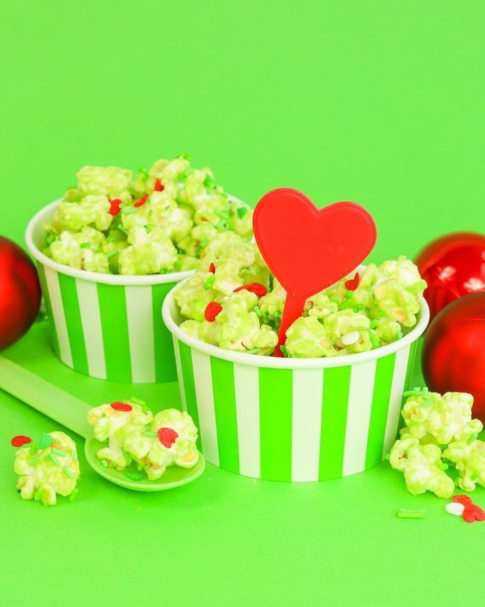 Grinch Popcorn in stripe green ice cream cups with red heart cupcake pick.