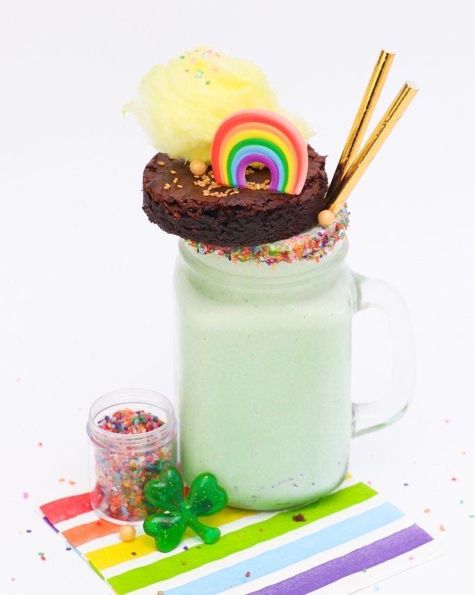 green freakshake in glass mug with sprinkles and topped with brownie