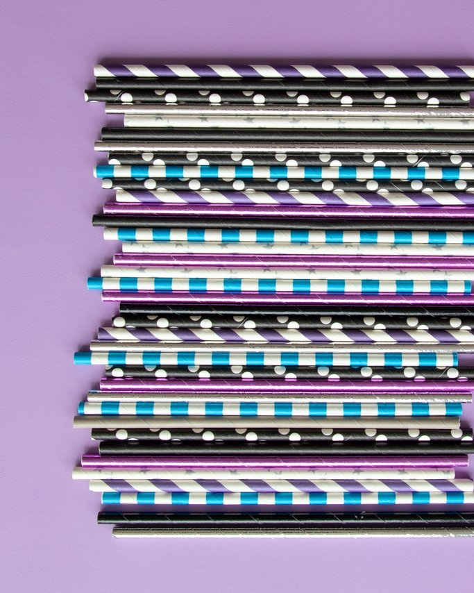 Assorted galaxy themed party paper straws on purple background
