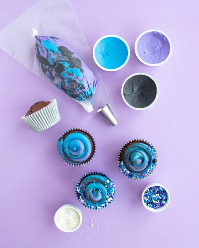 DIY Galaxy Party Cupcakes Tutorial with blue, purple, black buttercream and piping bag full of swirl buttercream