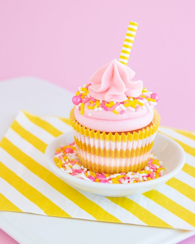 Pink lemonade cupcake topped with sprinkles and paper straw on plate of sprinkles