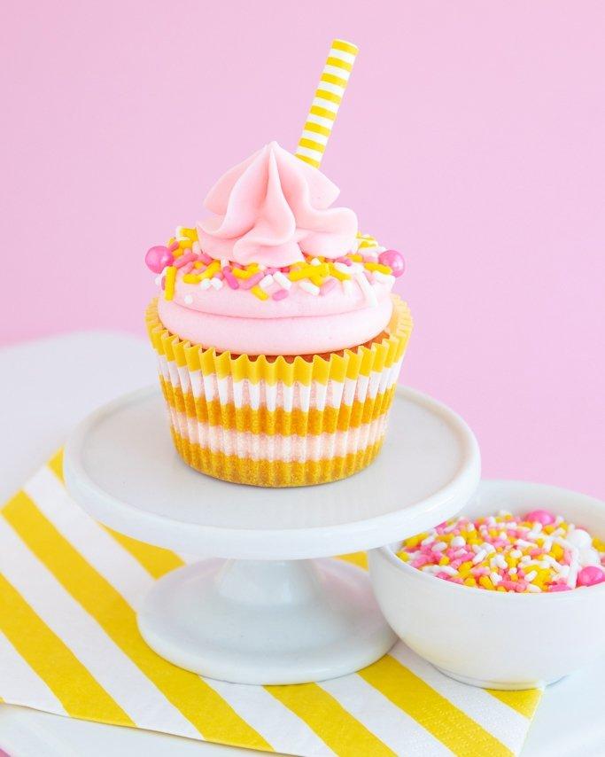 Pink lemonade cupcakes on white cupcake plate