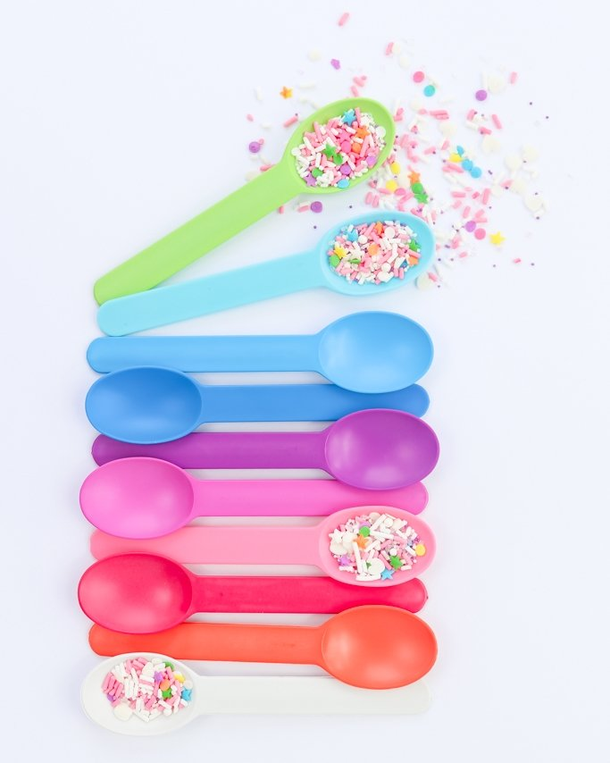 Plastic party spoons in all rainbow colors with sprinkles