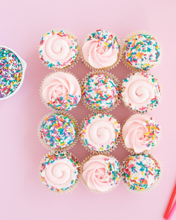 Frosted cupcakes with sprinkle dish for covering cupcakes with sprinkles