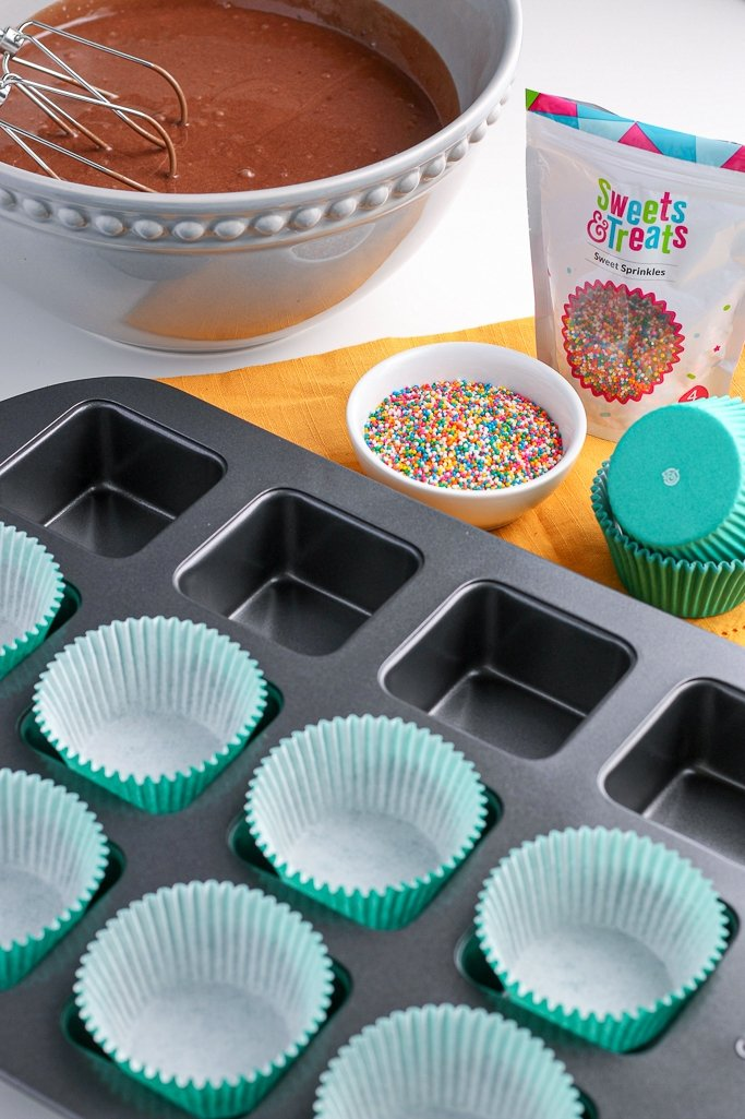 Square cupcake pan being prepared with liners for recipe.