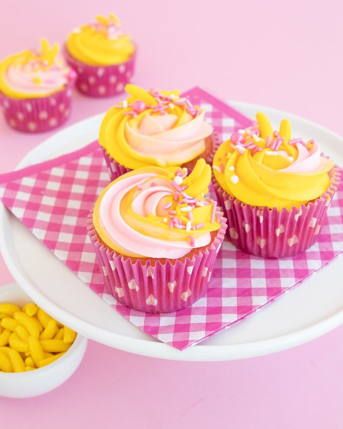 pink and yellow strawberry banana cupcakes on white cake plate