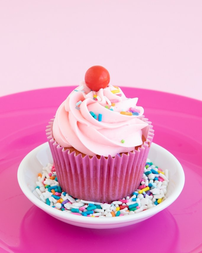 strawberry funfetti cupcake on plate of sprinkles