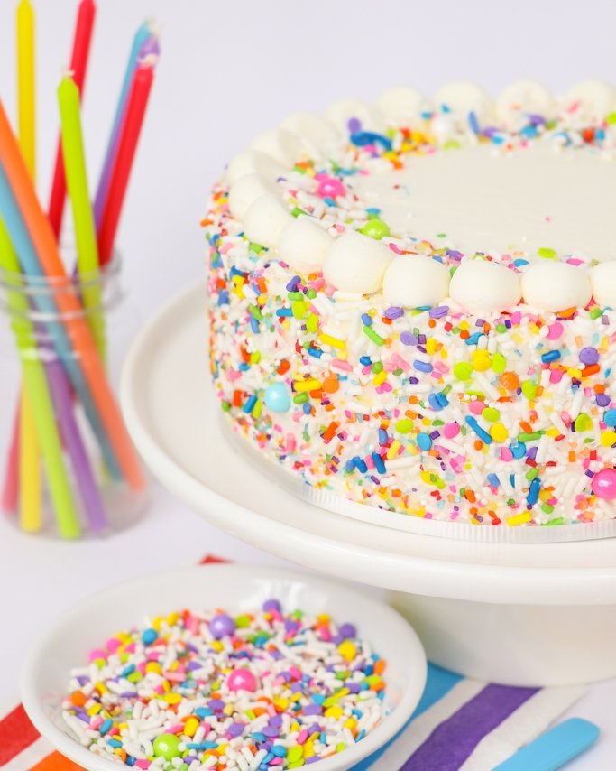 Unicorn covered rainbow sprinkle cake on white cake stand and candles in background