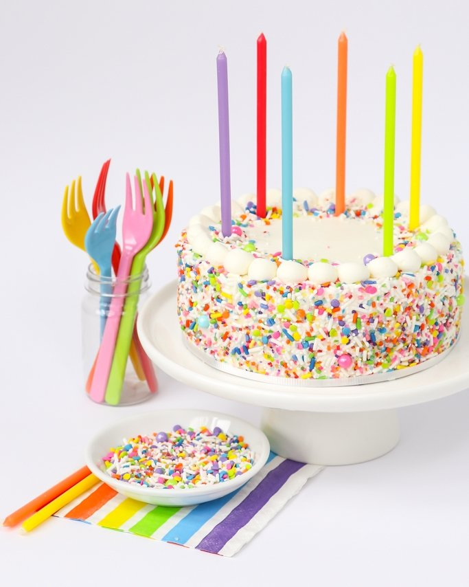 Unicorn Sprinkles on rainbow sprinkle cake with candles