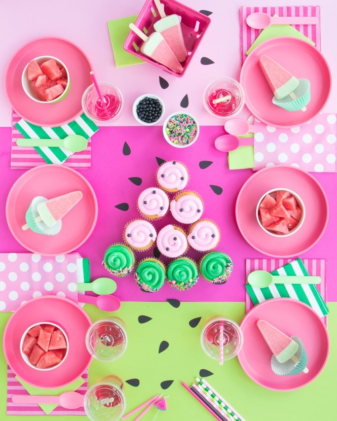 Watermelon Party Table with pink and green watermelon party supplies and watermelon sweets for watermelon party ideas.