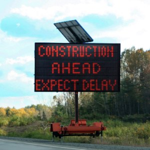 Construction delay warning sign next to a road