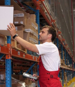 A worker with scanner in a warehouse maintaining stocks