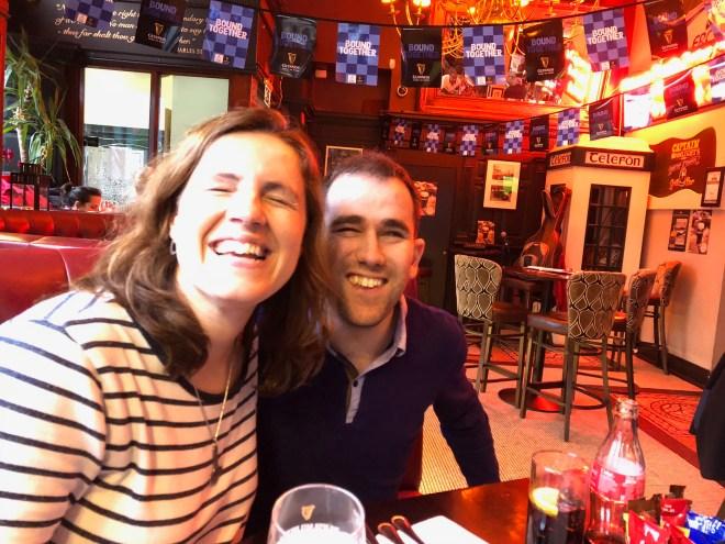 Juanjo y núria en primer plano sentados en un sofá en un pub sonriendo y de fondo una cabina telefónica de decoración y colgando del techo unos banderines.