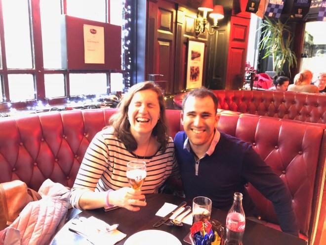 JJ y Núria sentados en el sofá del pub, de color rojo. Sonríen, Núria tiene una media pinta de cerveza y Juanjo una coca-cola y de fondo se ven cuadros en las paredes.