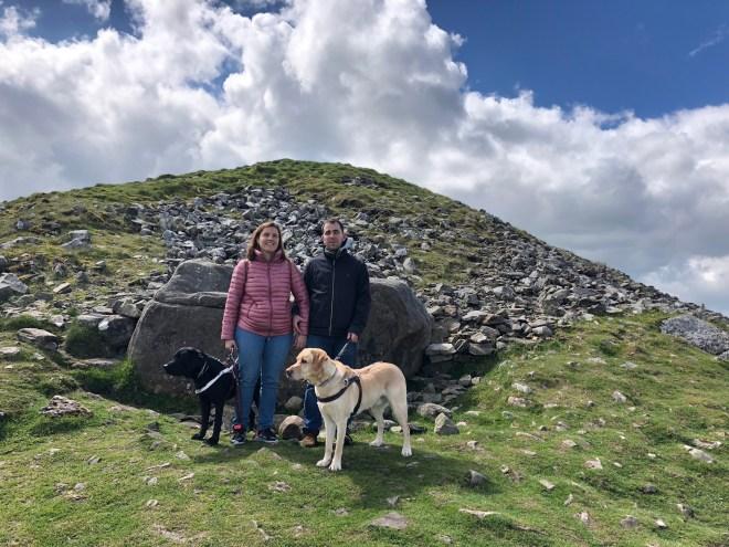 Juanjo y Núria en la cima de la colina en uno de los túmulos de piedra mirando a cámara y sus perros Oldo y whost mirando hacia la derecha.