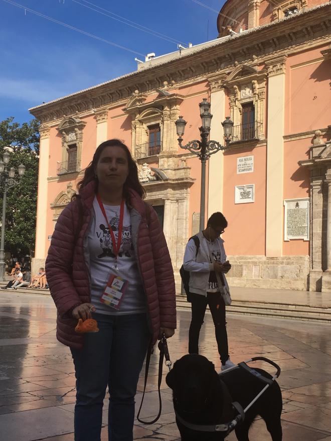 Chica ciega con su caracol viajero y su perro guía en la Plaza de la virgen.