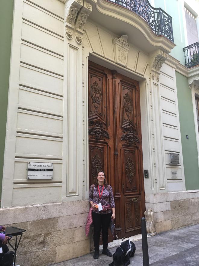 Chica ciega con su caracol viajero y su perro guía en el casco antiguo de Xàtiva delante de una casa noble antigua.