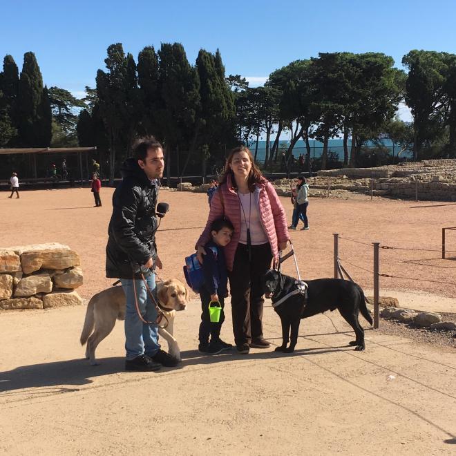 Juanjo, Núria abrazando por los hombros al pequeño Vikingo y nuestros dos perros guía.