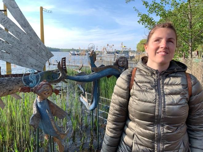 Núria con su perro guía a la derecha de la imagen, y se ve el embarcadero con figuras de madera de una sirena, un caballito de mar...
