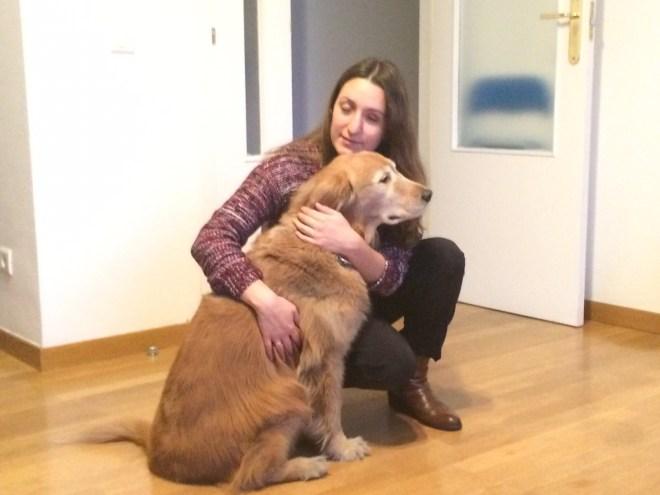 Patricia con su perrita guía Brilyn, una golden, en un salón.