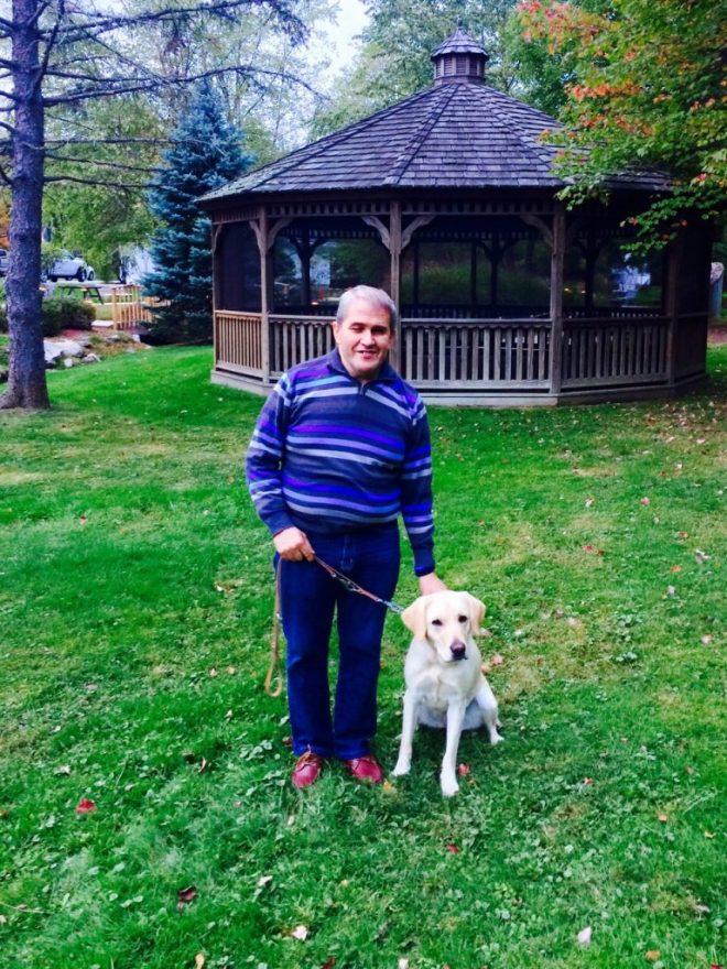 Angel con su perrita guía Meg en los jardines de la escuela de perros guía de Nueva York.