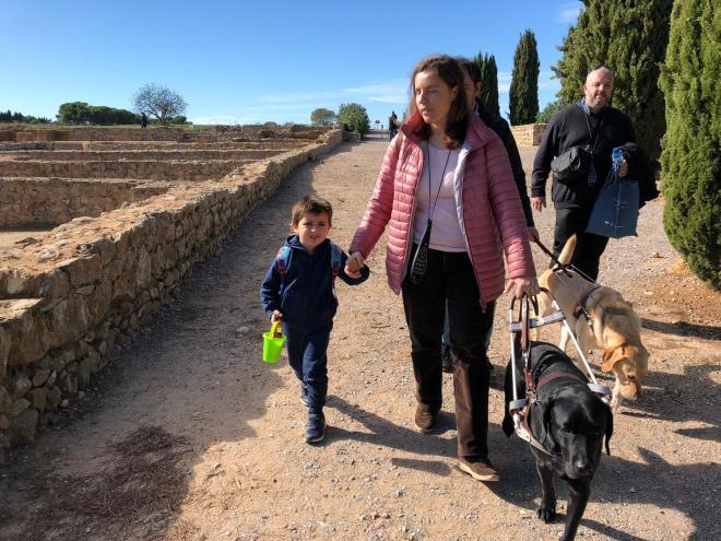 Núria con su perro guía y una audioguía colgada al cuello, el pequeño Vikingo de su mano todos de primer plano y detrás Juanjo con su perro guía, paseando por las ruinas de empúries.