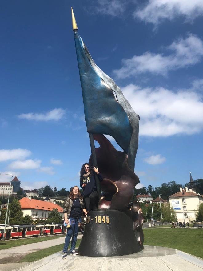 Núria y su prima con una escultura de la bandera de Praga.