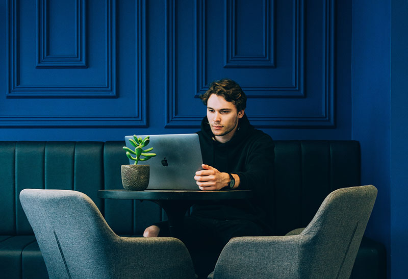 A man sitting with his laptop at a table