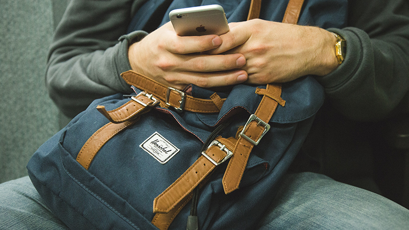 A person wearing a blue backpack while texting.