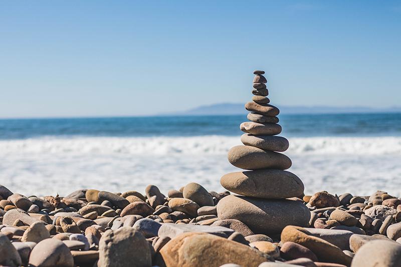 Rocks stacked on the beach near the ocean.