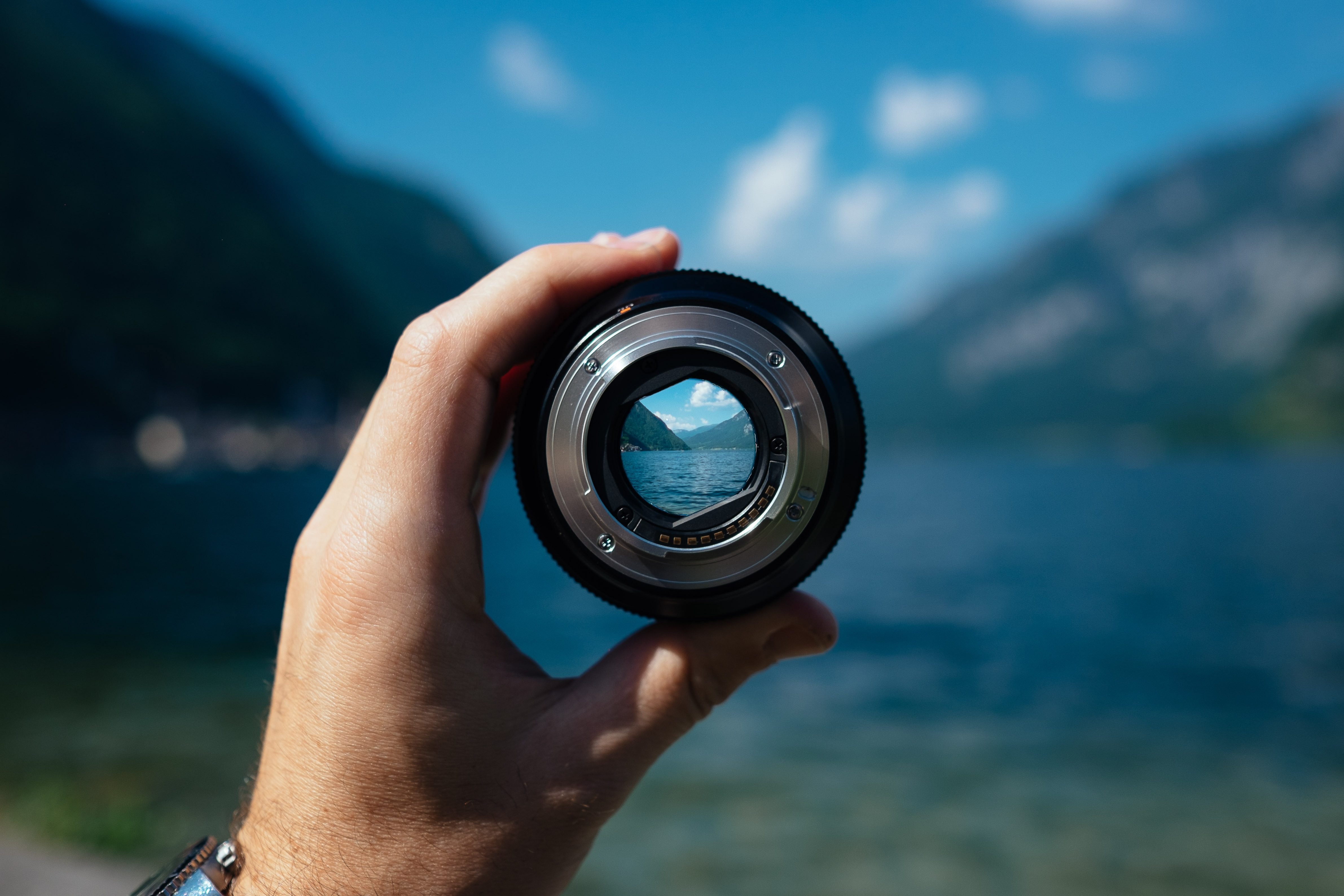 A person holds up a focusing lens in front of a lake and mountains.