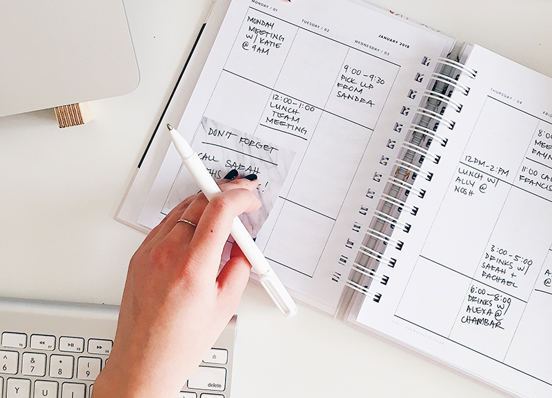 A person places a sticky note into a calendar planner. Proper appointment and event reminders help you improve your business process.