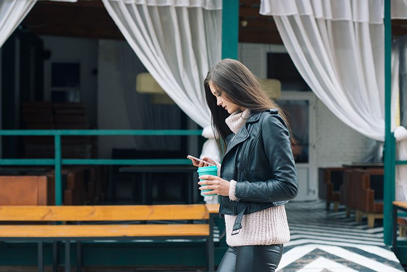 A woman walking while looking at her phone and holding a coffee cup. To get more engagement with customers, you need to have real conversations.