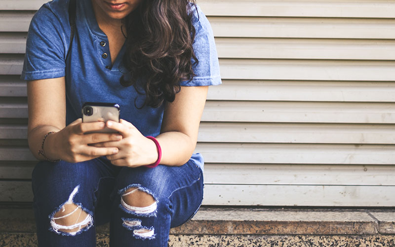 A woman wearing blue jeans and a blue shirt sits on a ledge typing on a phone.
