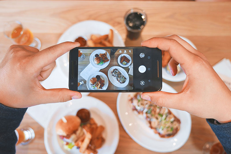 A person taking a photo of a table of food.