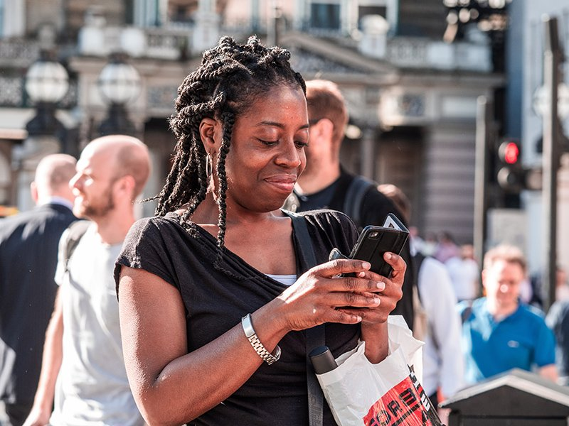 Black woman looking at her phone in a busy street and smiling.