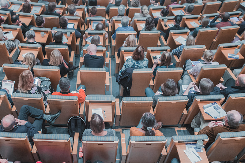 People sitting in chairs in a large lecture hall room.