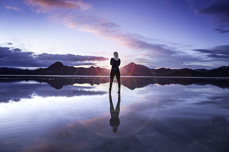 A woman standing on the salt flats at sunset.