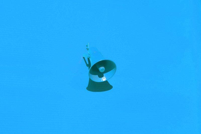 A blue megaphone on a blue background.