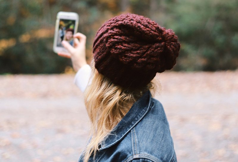 A woman wearing a red beanie taking a selfie. Using the right type of photos is part of branding your business texting.