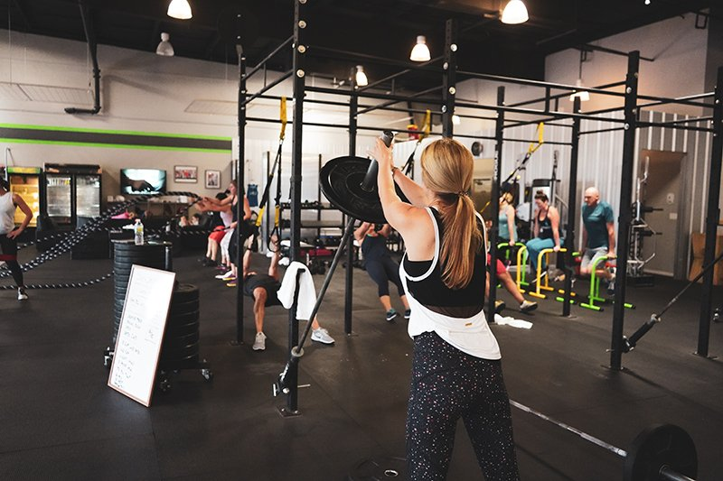 A woman lifting up a weight bar with a weight on the end in a crossfit-style gym.