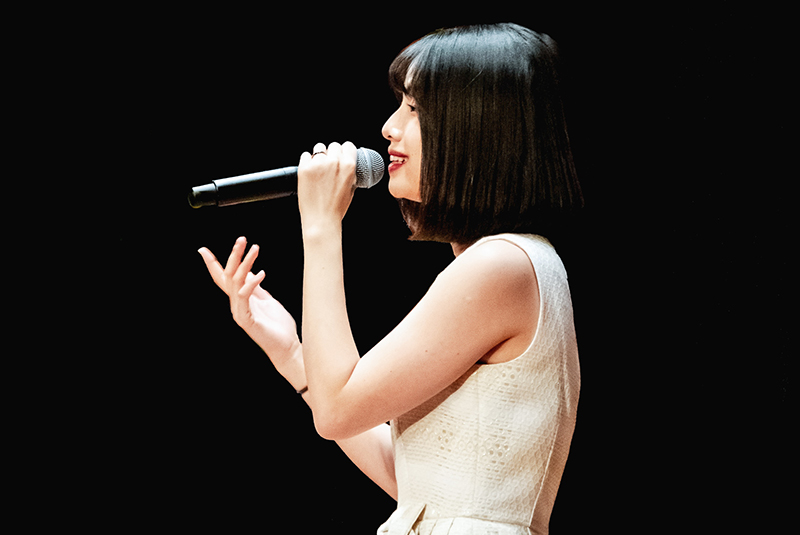 Woman with short black hair and a white dress holding a microphone speaking and gesturing with her other hand.