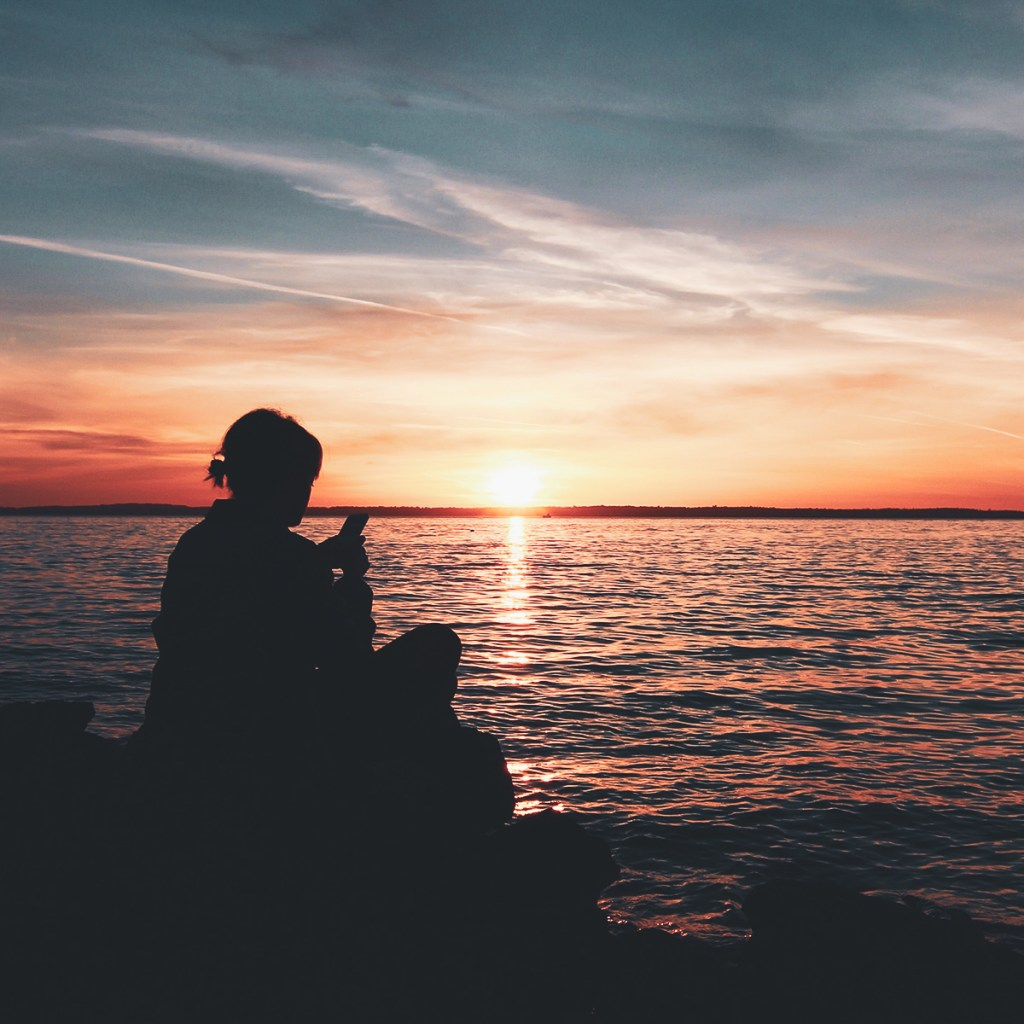 A silhouette of a person on their phone sitting next to a body of water at sunset.