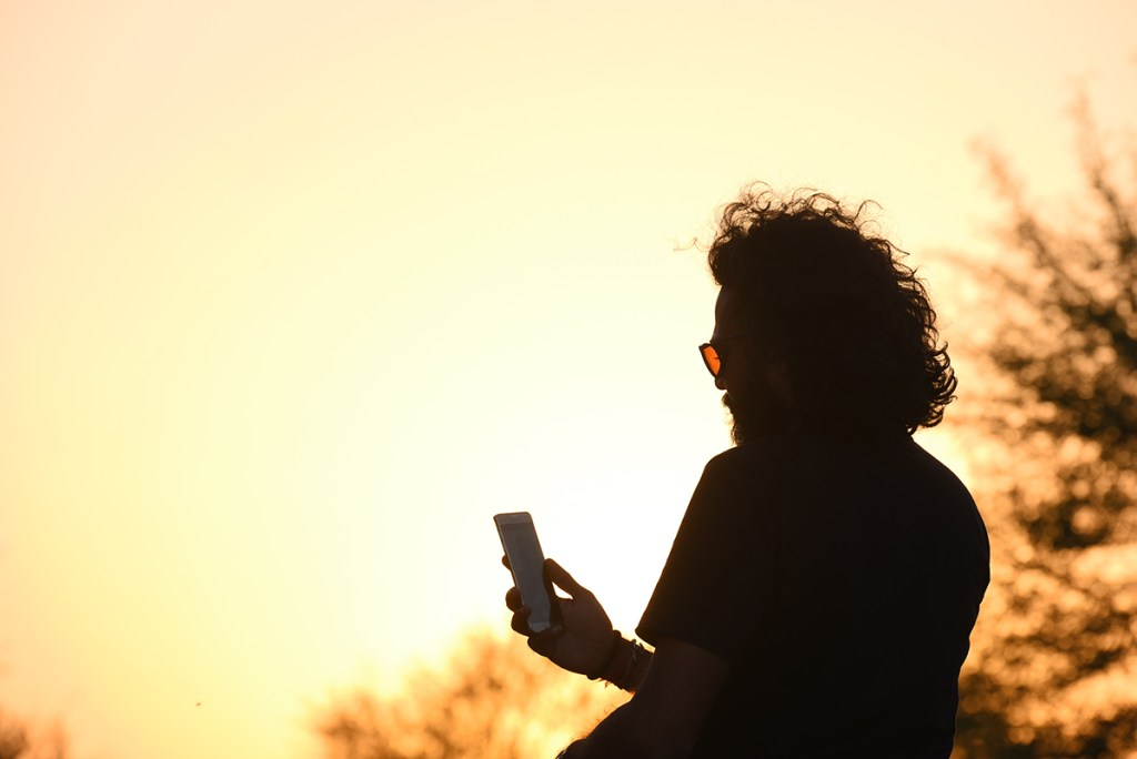 A man with wavy long hair looks at their phone as the sun is setting behind them.