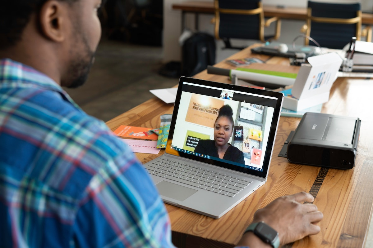 A Black sales professional sitting at a desk while on a video call with a Black woman sales professional.
