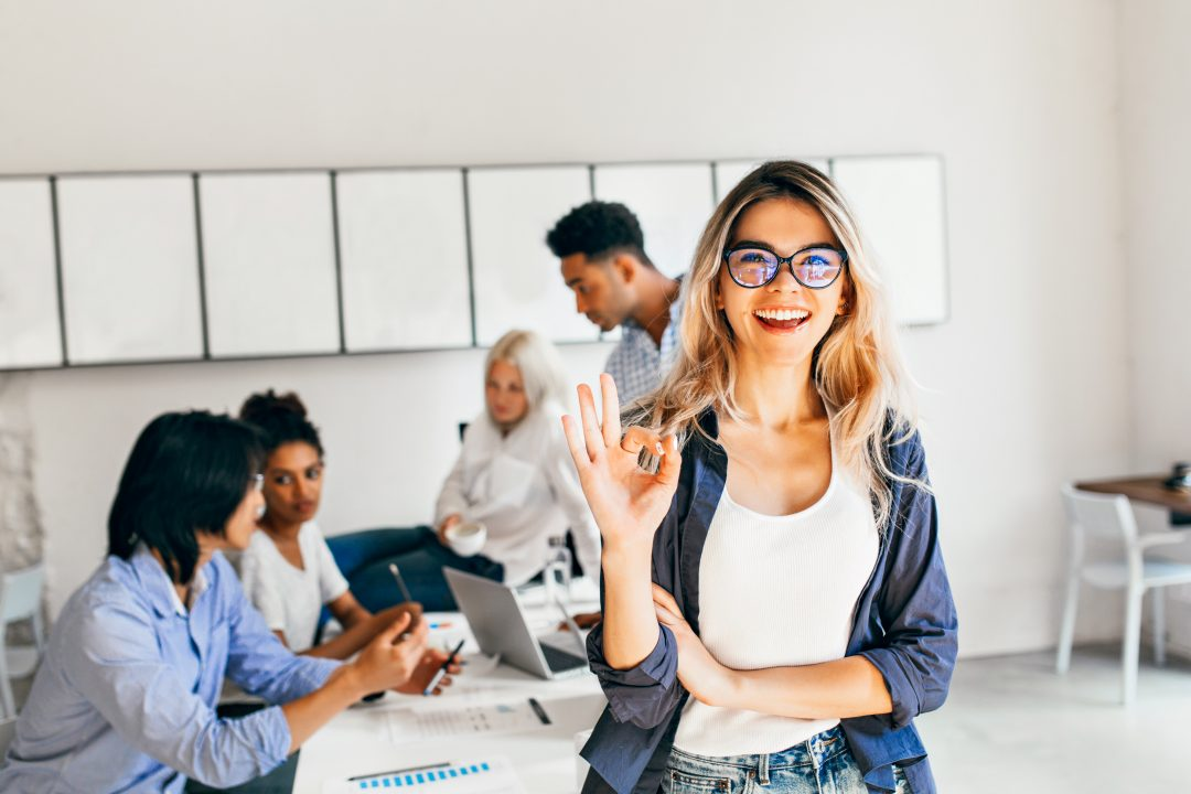 Woman with blond hair and glasses doing an OK sign while a team of four people works on a computer behind her.
