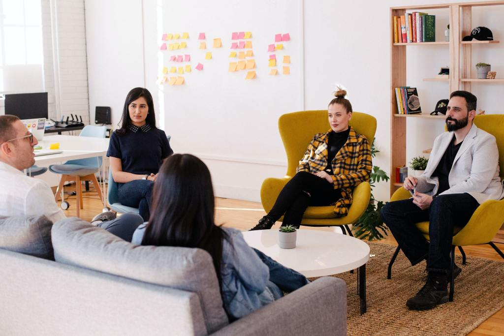 A group of 5 people, 3 women and 2 men, sits in a circle in an office talking and collaborating.